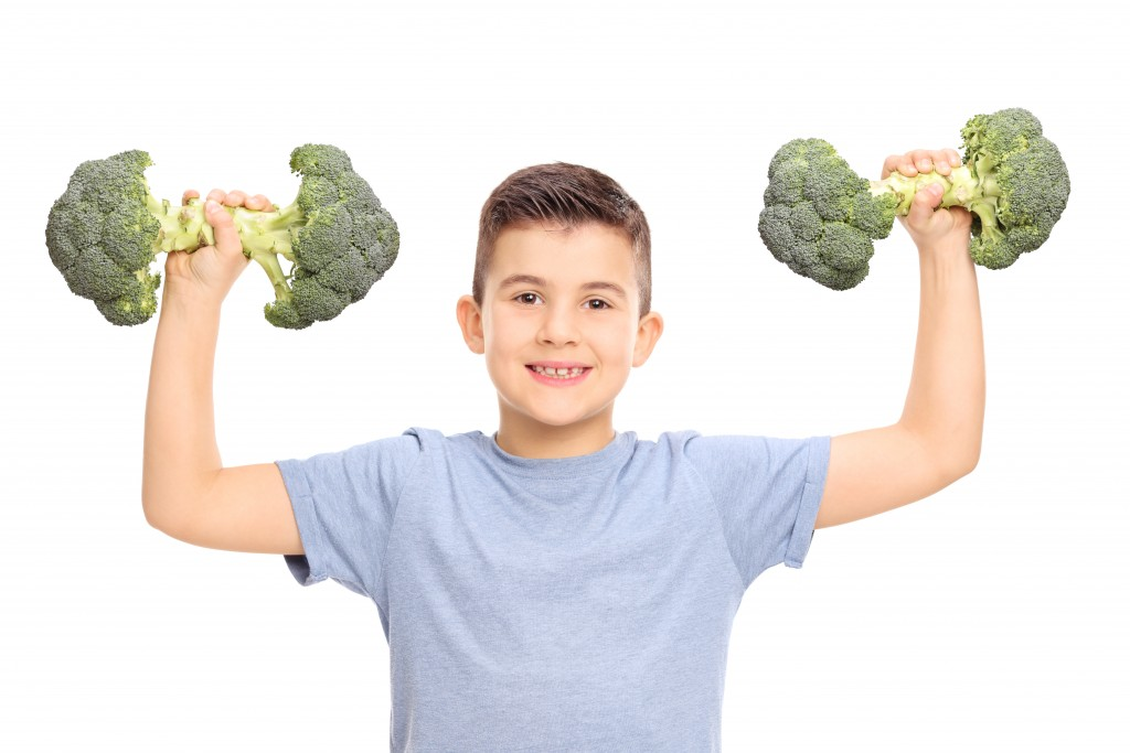 Little kid holding two broccoli dumbbells isolated on white background